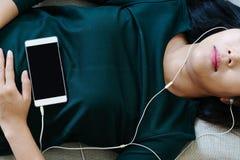 Över huvudet sikt av den härliga unga kvinnan som lägger ner på soffan genom att använda smartphonen för att lyssna musiken arkivfoto