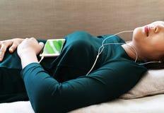 Över huvudet sikt av den härliga unga kvinnan som lägger ner på soffan genom att använda smartphonen för att lyssna musiken arkivbild