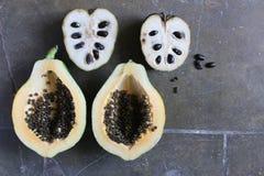 Över huvudet sikt av den halva papayaen och cherimoyaen Arkivbilder