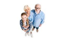 Över huvudet sikt av den lyckliga farfadern, farmodern och barnbarnet som kramar och ser kameran Royaltyfria Bilder