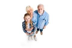 Över huvudet sikt av den lyckliga farfadern, farmodern och barnbarnet som kramar och ser kameran Royaltyfri Bild