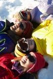 Över huvudet sikt av den tonårs- familjen som ligger i Snow royaltyfri fotografi