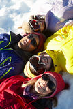 Över huvudet sikt av den tonårs- familjen som ligger i Snow arkivfoton