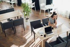 Över huvudet sikt av den unga kvinnan som bär en smartwatch som arbetar på hennes bärbar dator på ett kafé Den bästa sikten sköt  Royaltyfri Bild