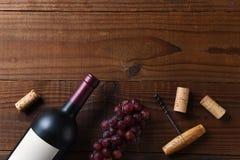 Över huvudet sikt av en Cabernet - sauvignon vinflaska på en mörk träyttersida med druvor och att korka skruvkorkar och kopiering arkivfoto