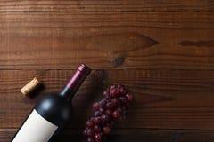 Över huvudet sikt av en Cabernet - sauvignon vinflaska på en mörk träyttersida med druvor och kork- och kopieringsutrymme fotografering för bildbyråer