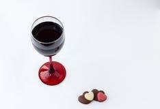 Över huvudet sikt av ett exponeringsglas av vin med två hjärtachoklader Arkivfoto
