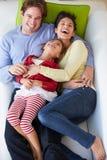 Över huvudet sikt av familjen som kopplar av på soffan royaltyfri fotografi