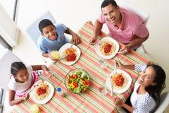 Över huvudet sikt av familjen som tillsammans äter mål arkivbilder