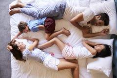 Över huvudet sikt av familjen som tillsammans ligger i säng Arkivfoto