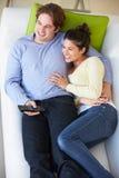 Över huvudet sikt av hållande ögonen på TV för par på soffan royaltyfria foton