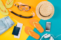 Över huvudet sikt av kläder, flipmisslyckanden, biljetter, hörlurar, smartphone och snorklautrustning Royaltyfri Fotografi