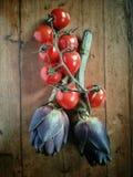Över huvudet sikt av kronärtskockor och tomater Arkivbild