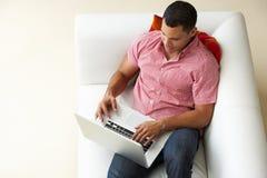 Över huvudet sikt av mannen som kopplar av på Sofa Using Laptop royaltyfri fotografi