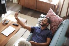 Över huvudet sikt av mannen som ligger på Sofa At Home Posing For Selfie på mobiltelefonen arkivfoto
