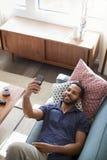 Över huvudet sikt av mannen som ligger på Sofa At Home Posing For Selfie på mobiltelefonen royaltyfri fotografi