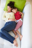 Över huvudet sikt av modern och dottern som kopplar av på soffan Royaltyfria Foton