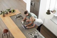 Över huvudet sikt av par som ser bärbara datorn i modernt kök Royaltyfri Bild
