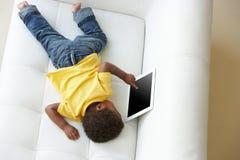 Över huvudet sikt av pojken på Sofa Playing With Digital Tablet royaltyfria foton