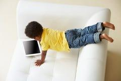 Över huvudet sikt av pojken på Sofa Playing With Digital Tablet Royaltyfri Foto