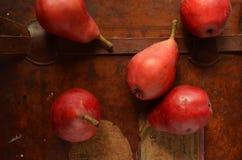 Över huvudet sikt av röda päron på tappningläderresväskan Royaltyfri Fotografi