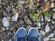 Över huvudet sikt av skor på grå färgstenjordning Skor på en stenbakgrund Gymnastikskor på ett stengolv Sportkondition skor skodo Royaltyfria Bilder