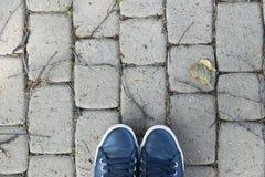 Över huvudet sikt av skor på grå färgstenjordning Skor på en stenbakgrund Gymnastikskor på ett stengolv Sportkondition skor skodo Arkivfoton