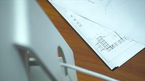 Över huvudet sikt av skrivbordet för arkitekt` s med ritningar och datoren materiel Bästa sikt av ett funktionsdugligt skrivbord: arkivfoton