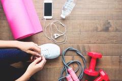 Över huvudet sikt av sport- och konditionkvinnan som binder skor med mobila enheter och sportutrustningar på trä arkivfoton