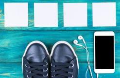 Över huvudet sikt av sportskor vid mobiltelefonen med isolerad skärm- och i-öra hörlurar och vita tomma tomma ark Royaltyfria Bilder