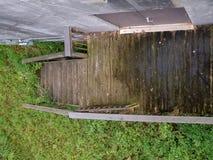 Över huvudet skott av trägångbanan som leder till den rostiga dörren i misstänksamt skogsbevuxet område royaltyfri fotografi