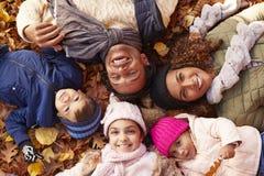 Över huvudet stående av familjen som ligger i Autumn Leaves royaltyfri fotografi
