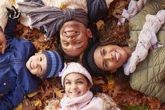 Över huvudet stående av familjen som ligger i Autumn Leaves Royaltyfria Foton