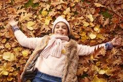 Över huvudet stående av flickan som ligger i Autumn Leaves arkivfoton