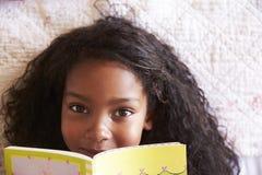 Över huvudet stående av flickan som ligger på säng och läseboken royaltyfri bild