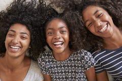 Över huvudet stående av tre tonårs- systrar som hemma ligger på säng royaltyfri bild