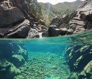 Över och den undervattens- floden vaggar med klart vatten Royaltyfria Bilder