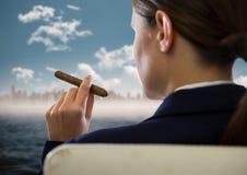 Över skuldra av den placerade affärskvinnan som röker cigarren och ser oskarp horisont och vatten Arkivfoton