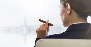 Över skuldra av den placerade affärskvinnan som röker cigarren och ser oskarp vit horisont Royaltyfri Bild