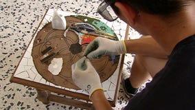 Över skuldrafors på konstnärhänder, när arbeta med mosaiken stock video