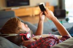 Över skuldran av grabben som lyssnar till musik från telefonen royaltyfria foton