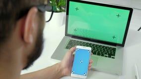 Över skuldran som skjutas av en ung caucasian man som hemifrån arbetar på en bärbar dator, grön skärmchromatangent 20-tal 4k lager videofilmer