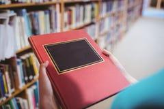Över skuldrasikt av studenten i bok för arkivinnehav royaltyfri bild
