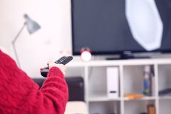 Över skuldrasikten av flickasammanträde på den hållande tvfjärrkontrollen för soffa och surfaprogram på television Problem av slö fotografering för bildbyråer