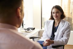 Över skuldrasikten av mannen som har konsultation med kvinnlig doktor In Hospital Office arkivfoton