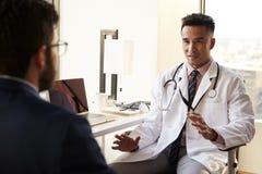 Över skuldrasikten av mannen som har konsultation med manlig doktor In Hospital Office royaltyfria bilder