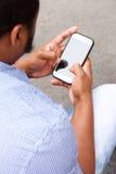 Över skuldraståenden av mannen som ser mobiltelefonskärmen Arkivfoto