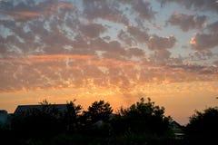 Över taken av den härliga solnedgången för hus som, om utdraget vid en artist& x27; s-borste som hälls av olika färger Arkivbild