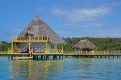 Över vattenbungalow med halmtäcka det karibiska havet för taket Arkivbilder