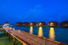 Över vattenbungalower med moment in i den fantastiska gröna lagun arkivfoto